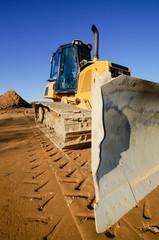 Baubranche - Baufahrzeug, Bulldozer auf einem Baugrundstück