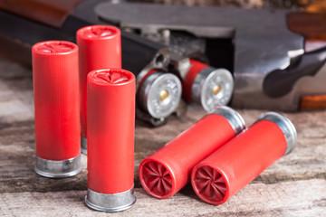 12 gauge shotgun shells with shotgun on wood surface