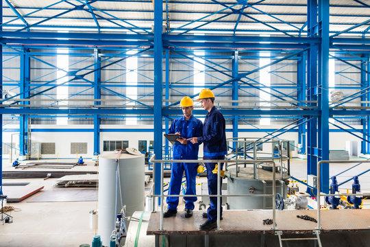 Workers in large metal workshop checking work