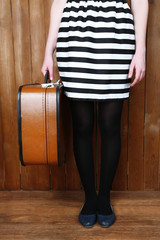 Woman holding old suitcase on wooden background