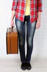 Woman holding old suitcase on brick wall background