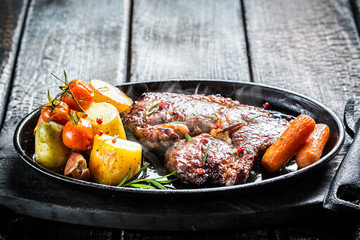 Roasted vegetables and steak with fresh herbs on barbecue dish