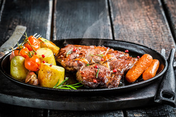 Roasted vegetables and steak with herbs on barbecue dish