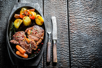 Roasted steak and vegetables with fresh herbs on barbecue dish