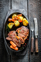Roasted steak and vegetables with herbs on barbecue dish