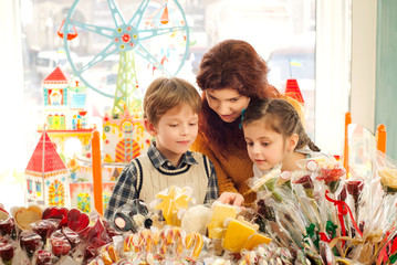 Mother with happy children in the candy store