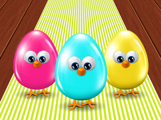 three colored Easter eggs standing on tablecloth