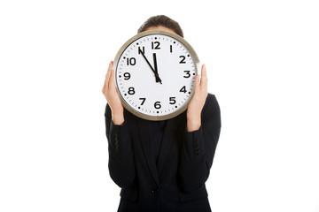 Businesswoman holding a big clock.