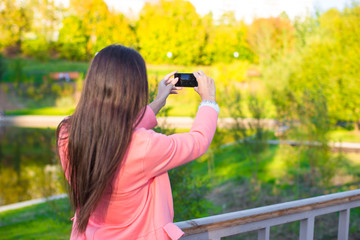 Young woman take a photo by her phone at autumn day
