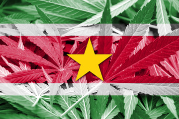 Suriname Flag on cannabis background. Drug policy.
