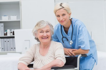 Nurse leaning on senior patients wheelchair at clinic