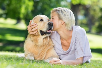 Pretty blonde kissing her dog in the park