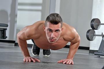 Hombre ejercitando haciendo flexiones en un gimnasio.