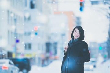 冬の街角に立つ女性