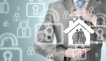 businessman protecting family in home with hands