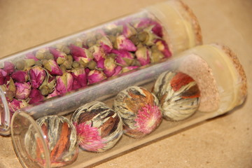 Tea rose buds and jasmine flowers in a glass container