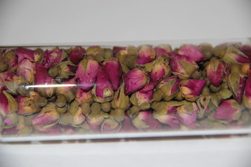 Tea rose buds flowers in a glass container