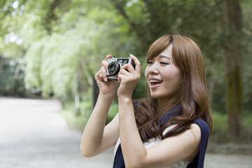 A woman in a Kyoto park holding a camera.