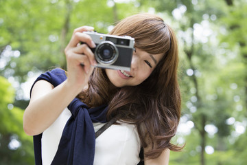 A woman in a Kyoto park holding a camera and laughing.