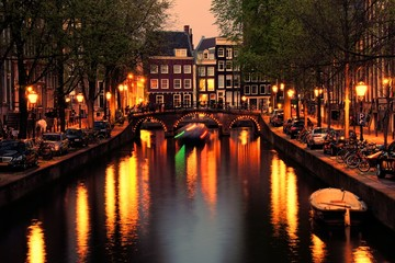 Fotomurales - Canals of Amsterdam with bridge lit at night, Netherlands