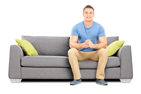 Handsome young man sitting on a modern sofa