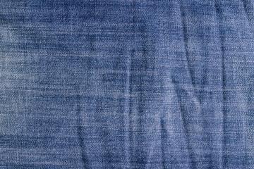 Crumpled vintage jeans texture, blue jeans background.