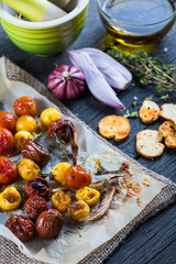 Freshly roasted vegetables with herbs on wooden table