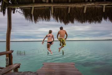 Beautiful couple in love jumping and having fun Bacalar lake. Ri