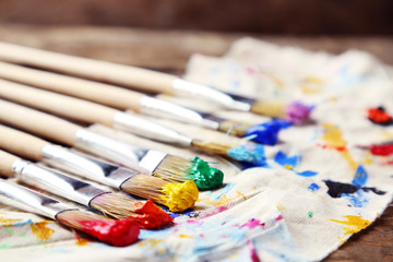 Brushes with colorful paints on dirty cloth