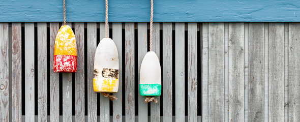 lobster buoys on weathered wood fence. Banner format
