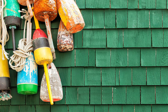 Lobster buoys hanging on a green shingled wall