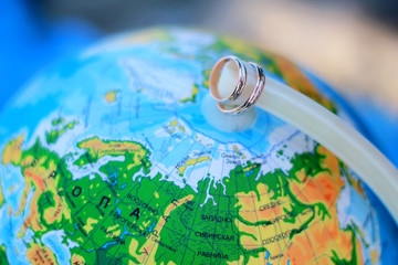 wedding rings on a background of the globe, world map