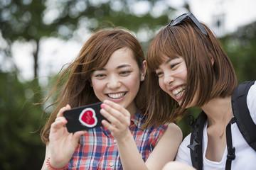 Two women, friends, taking a selfie in the park.
