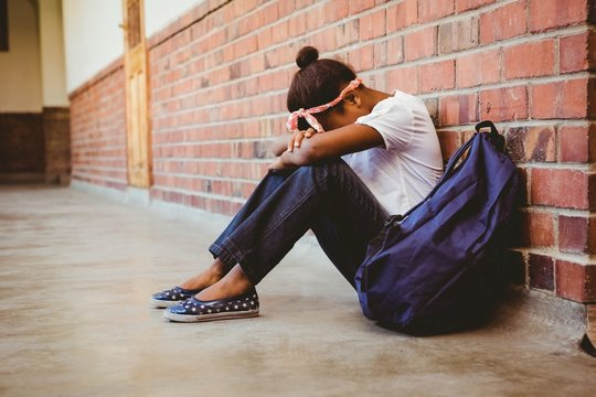 Tensed mixed race girl sitting against brick wall in school corridor