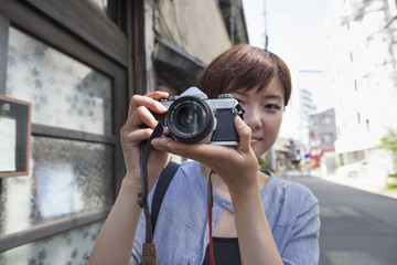 A woman taking a picture with camera while standing outdoors