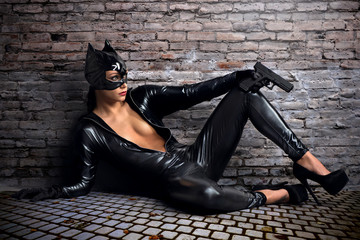 Sexy female in black catwoman costume with gun