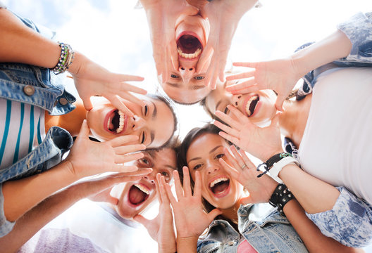 group of teenagers looking down and screaming