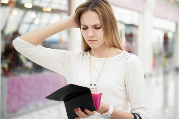 Confused young woman checking her purse after spending too much