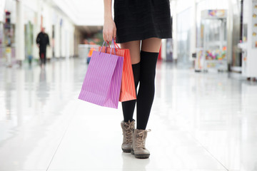 Walking with shopping bags, close up of female legs