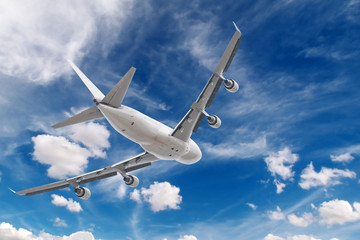 big jet plane flying on blue cloudy skybackground