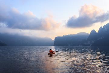 Men paddling canoes at Cheow Lan Lake.