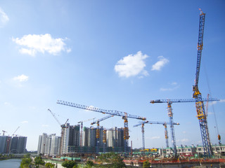 Modern buildings under construction and cranes under a blue sky