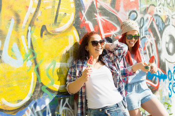 Two teenage friends eating ice-cream outdoors in summer