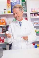Smiling senior pharmacist holding prescription and jar