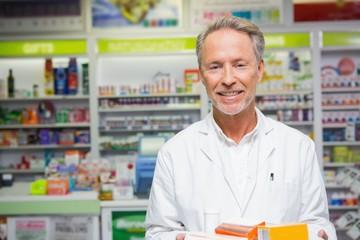 Senior pharmacist holding many medicines