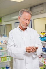 Concentrated pharmacist looking at medicine