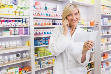 Smiling pharmacist on the phone reading prescription