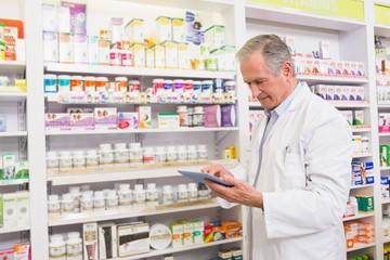 Senior pharmacist using tablet pc