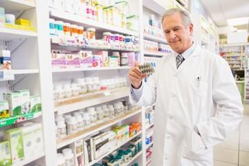 Papiers peints Pharmacie Smiling senior pharmacist holding blister