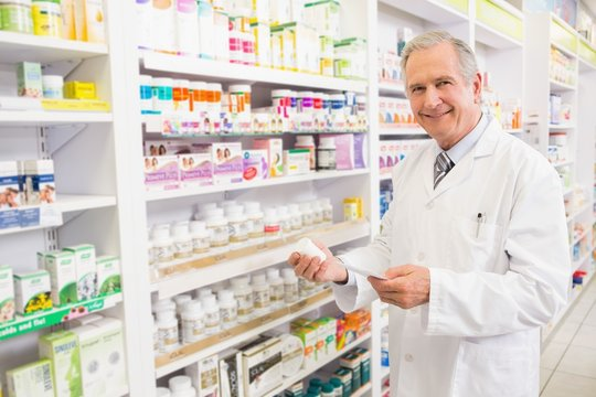 Smiling senior pharmacist holding medicine and prescription